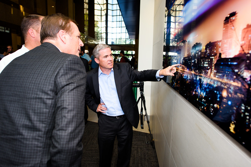 """Brian Pearce, Senior Vice President of Real Estate Services for Unico Properties, inspects the newly unveiled artwork. Unico Properties hosts an art installation of the 25-foot wide, three-panel panoramic photo of downtown photo in U.S. Bancorp Tower lobby on June 29, 2016. Taken by Portland photographer Michael Cary Arellano and printed directly on metal, """"Above the Clouds"""" is the largest metal photograph ever sold in the U.S. (Credit: Molly J. Smith)"""
