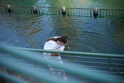 A young girl deciding whether to venture into the channel full of catfish.