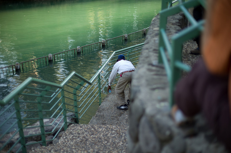 A man filling a coke bottle with water from the River Jordan.