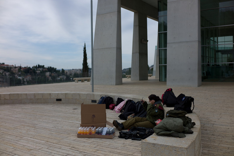 A soldier minding both the cases of juice, packs and guns of her unit at Yad Vashem.