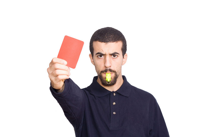 """Licensed still image. Ref represents the enforcer of rules. Good image because it has white background that will provide striking """"at rest"""" first image in the vid player, and will transition to the """"rules"""" or """"redtape"""" images well.Dominant red card plays the red theme. [5966525_refredcard]"""