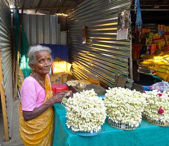 A sweet elderly lady selling garlands