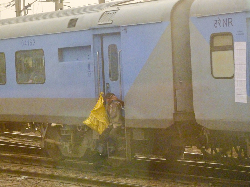 Young boy collecting trash from the train