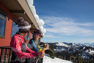 two women relax on the summit house deck at Whitefish Mountain Resort with glacier national park in the background.