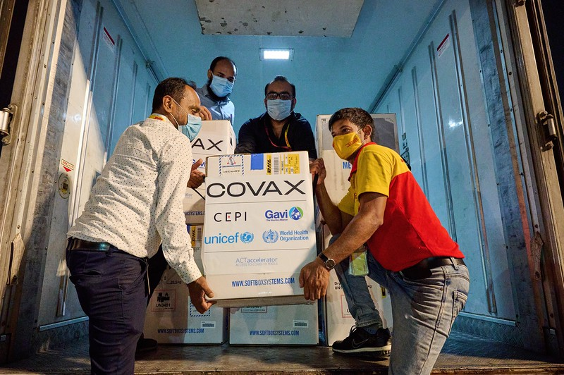 """0009-0013COVAX-31-05-2021-UNICEF COVAX First Vaccines Arrival in Bangladesh.   Bangladesh receives its first shipment of COVID-19 vaccines from the COVAX Facility led by directed by Gavi, CEPI, WHO and UNICEF on 31 May 2021. The arrival of the first vaccines from the COVAX Facility is a major moment for equitable distribution in Bangladesh and will bolster the country's immunization effort to protect health workers, teachers, the elderly and people most at risk.   The consignment of over 100,000 Pfizer COVID-19 vaccines are unloaded at Hazrat Shahjalal International Airport in Dhaka for transportation to the cold chain storage facility at the Institute of Public Health. Logistics specialists monitor the process to ensure the cold chain is preserved and the vaccines are handled safely at every step.   Bangladesh joins over 100 countries and areas that have received lifesaving vaccines through COVAX - marking a major milestone in the race to provide vaccines to all countries.  Unloading of the """"COVAX"""" COVID-19 vaccines supplies and being transported from the airport to the cold storage facility at Center for Medical Biotechnology (CMBT) at Hazrat Shahjalal International Airport, Dhaka, Bangladesh on 31st May,2021. Photo: UNICEF / b.a.sujaN / Map"""