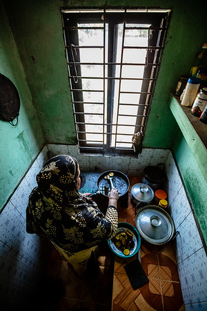 """BD-RMG-Mahfuja-0015  """"Girls are more neglected and under constant pressure. This is because people think that girls are not capable of doing the same amount of work as a man,"""" says Mahfuza Begum (31) while cooking in the kitchen for her family. Mahfuza Begum (31) is the union leader in a garments factory where she has been working for the past 15 years. She is fighting to ensure that no workers are wrongfully treated in the workplace and they receive all the benefits proclaimed by the country's government.  E.P.Z. Road, Ashulia, Dhaka-1349. Bangladesh.  Photo Credit: b.a.sujaN / Plan International / Map Photo Agency, Dhaka, Bangladesh."""