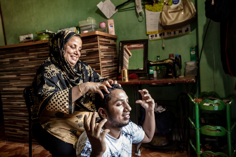 BD-RMG-Mahfuja-0019  Mahfuza Begum (31) applying coconut oil and massaging her eldest son, Tipu's (15), scalp which he loves. She does this every weekend and they catch up regarding Tipu's work and his plans. Mahfuza Begum (31) is the union leader in a garments factory where she has been working for the past 15 years. She is fighting to ensure that no workers are wrongfully treated in the workplace and they receive all the benefits proclaimed by the country's government.  E.P.Z. Road, Ashulia, Dhaka-1349. Bangladesh.  Photo Credit: b.a.sujaN / Plan International / Map Photo Agency, Dhaka, Bangladesh.