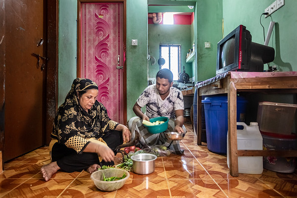 """BD-RMG-Mahfuja-0014  """"I had my eldest son when I was 16 years old. It fills me up with pride to see him get a good education and be able to work in an office,"""" says Mahfuza Begum during the preparation of a meal for the family, while her eldest son Tipu (15) helps her.  Mahfuza Begum (31) is the union leader in a garments factory where she has been working for the past 15 years. She is fighting to ensure that no workers are wrongfully treated in the workplace and they receive all the benefits proclaimed by the country's government.  E.P.Z. Road, Ashulia, Dhaka-1349. Bangladesh.  Photo Credit: b.a.sujaN / Plan International / Map Photo Agency, Dhaka, Bangladesh."""
