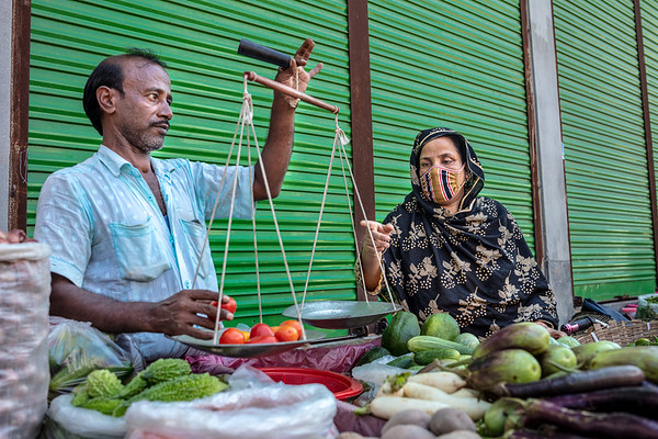 """BD-RMG-Mahfuja-0013  """"I would mostly walk from home to work and back again. And I would walk a distance of more than 5km every day, even if I was tired or running late. Because if I took a rickshaw, I would not be able to afford groceries for the day,"""" says Mahfuza Begum (31) while she was buying vegetables on her way back from work. Mahfuza Begum (31) is the union leader in a garments factory where she has been working for the past 15 years. She is fighting to ensure that no workers are wrongfully treated in the workplace and they receive all the benefits proclaimed by the country's government.  E.P.Z. Road, Ashulia, Dhaka-1349. Bangladesh.  Photo Credit: b.a.sujaN / Plan International / Map Photo Agency, Dhaka, Bangladesh."""