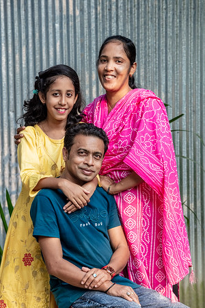 BD-RMG-Morzina-0017  Morzina (29), with her husband and their daughter, having a family portrait taken in their village home in Bogura. Morzina (29) is a garments factory worker and union leader. She advocates for women's empowerment in the workplace.   Bogura, Bangladesh. Photo Credit: b.a.sujaN / Plan International / Map Photo Agency, Dhaka, Bangladesh.