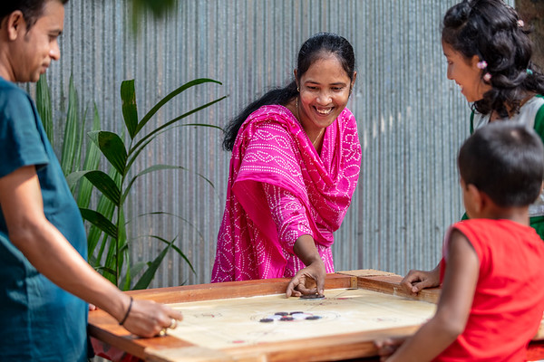 BD-RMG-Morzina-0016  Morzina (29), playing carrom with her husband and their daughter in their village home in Bogura. Morzina (29) is a garments factory worker and union leader. She advocates for women's empowerment in the workplace.   Bogura, Bangladesh. Photo Credit: b.a.sujaN / Plan International / Map Photo Agency, Dhaka, Bangladesh.