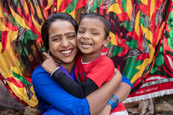 """BD-RMG-Romana-SF Danim-0023-0024  """"However long I work, I want to work well and not have to stress about my parents or my child,"""" says Romana (24) while she smiles for the camera with her son. Romana (24) is an operator at a garments factory as well as a union leader, fighting for workers rights.  Tejgaon Industrial Area, Dhaka-1208, Bangladesh.  Photo Credit: b.a.sujaN / Plan International / Map Photo Agency, Dhaka, Bangladesh."""