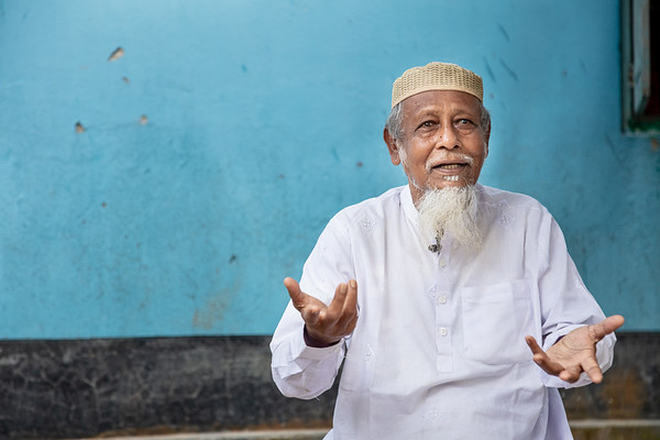"""BD-RMG-Father-In-Law-Morzina-0001-0004  Md. Alom Hossain, Morzina's father-in-law, supports his daughter-in-law in her endeavours and looks after her daughter while Morzina works in Dhaka. He is devoted to his granddaughter's upbringing and says """"My dream is to give her the highest level of education possible. If she studies she can become self-sustainable, she can have good jobs. She can become a doctor, or become an engineer. There will be no shortage of support from my end.""""   Bogura, Bangladesh. Photo Credit: b.a.sujaN / Plan International / Map Photo Agency, Dhaka, Bangladesh."""
