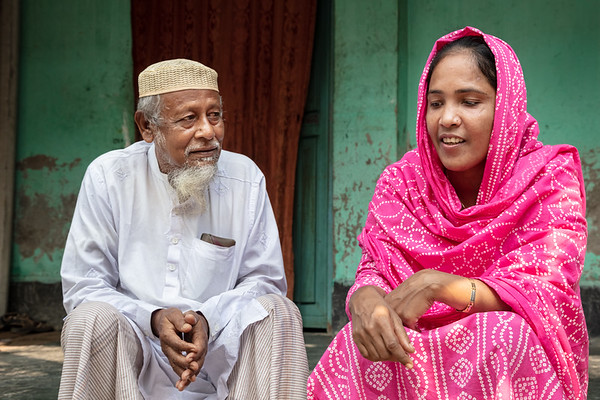 BD-RMG-Father-In-Law-Morzina-0005  Morzina and her father-in-law, Md Alom Hossain, catching up during one of her visits to her husband's village home in Bogura. They are very close, with Alom Hossain stating that rather than his son's wife, he considers Morzina his own daughter.   Bogura, Bangladesh. Photo Credit: b.a.sujaN / Plan International / Map Photo Agency, Dhaka, Bangladesh.