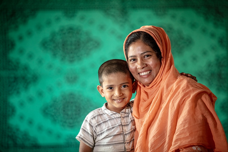 "BD-RMG-Monoara-Fatema Sweater Factory-0003  ""I have changed a lot since I first came to Dhaka. I have become stronger,"" says Monowara (26) as she poses for the camera with her son Nayem. Monowara (26) is a Ready-Made Garments worker, who also runs a small business embroidering clothing for companies from home.  Ashulia, Savar, Dhaka, Bangladesh.  Photo Credit: b.a.sujaN / Plan International / Map Photo Agency, Dhaka, Bangladesh."