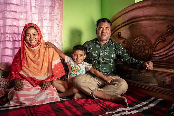 BD-RMG-Monoara-Fatema Sweater Factory-0018  Monowara (26) Posing for a family photo with her only son and husband.  Ashulia, Savar, Dhaka, Bangladesh. Photo Credit: b.a.sujaN / Plan International / Map Photo Agency, Dhaka, Bangladesh.