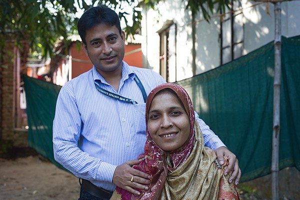 """Esmotara's husband-Md. Shafiqul Islam Khan-0004-0005  """"I am always there for Ismat Ara so that she can keep on doing the good work and rise higher than ever before. I admire her work very much and I always pray that she may achieve more in her life,"""" says Md. Shafiqul Islam Khan as he and his wife, Esmotara, have their portrait taken beside their home in Ashulia. Md. Shafiqul Islam Khan is a Safety Officer at a garments factory, as well as the husband of Esmotara, Chairman of the Worker's Union in the same factory.  Ashulia, Dhaka-1349. Bangladesh. Photo Credit: b.a.sujaN / Plan International / Map Photo Agency, Dhaka, Bangladesh."""