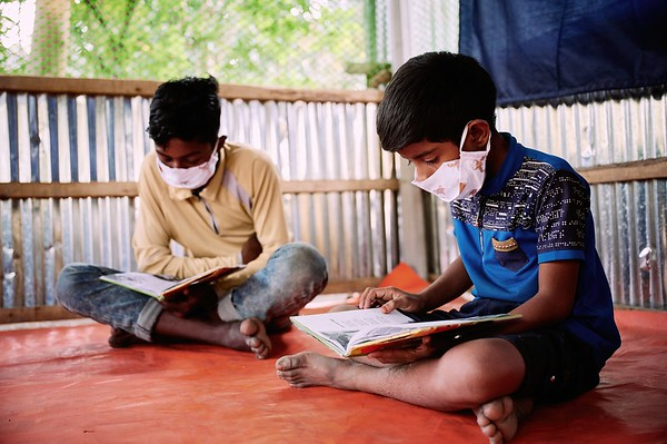 0009-WASH-22nd February -2021 Rafiqul,9, and Anisuzaman, 11, reading books inside the hub During COVID 19 pandemic. All schools are closed so UNICEF provided Child Protection & Emergency Flood Response Project Hub is the only place he can spend time with his friends. Supported by UNICEF, Implemented by GUK and GOV of Bangladesh.  Village Pachgachy, Zatrapur Union, Kurigram District, Bangladesh. Photo: Bashir Ahmed Sujan /Map