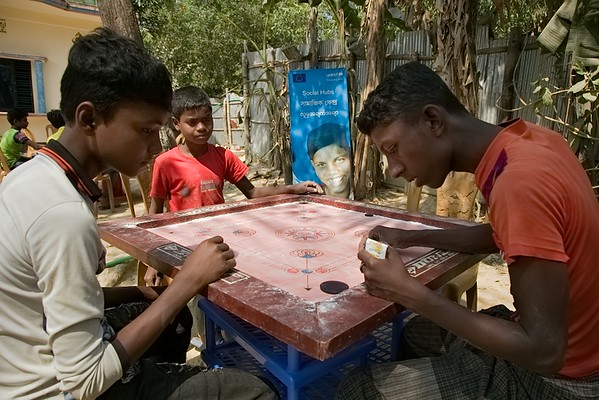 UNICEF-IcSP-SH-0390-0396  Children from Rohingya community playing Carrom board on the courtyard of Jadimura Social Hub for Adolescents. EU IcSP Social Hub, supported by UNICEF, Implemented by BITA. Near Camp 27,9 no word, Hnila, Teknaf, Cox's Bazar, Bangladesh. Photo: b.a. sujaN / UNICEF / Map