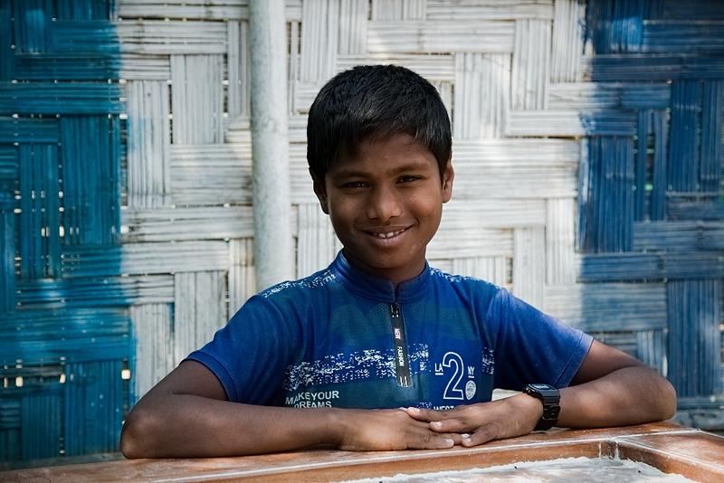 UNICEF-IcSP-SH-0017-0021  Abdul Mutalib (14), (Case Study) Playing Ceram Board with friends outside of EU IcSP Social Hub, supported by UNICEF, Implemented by BITA. Near Camp 15, Ukhia, Cox's Bazar, Bangladesh. Photo: b.a. sujaN / UNICEF / Map