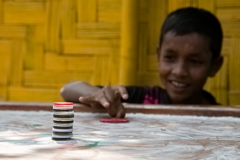 UNICEF-IcSP-SH-0022  Mohammad Ayub (11), Playing Ceram Board with friends outside of EU IcSP Social Hub, supported by UNICEF, Implemented by BITA. Near Camp 15, Ukhia, Cox's Bazar, Bangladesh. Photo: b.a. sujaN / UNICEF / Map