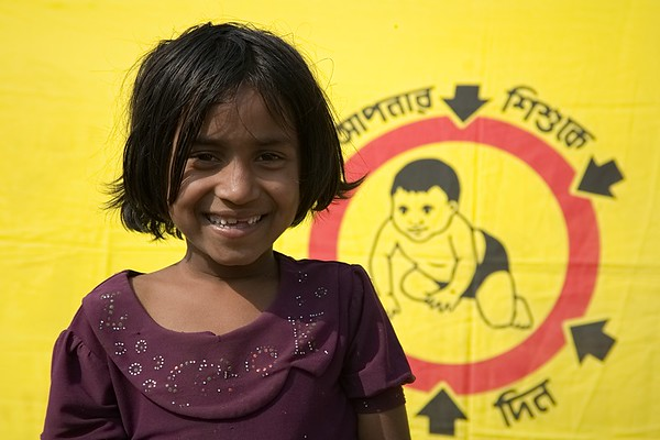 UNICEF-RR-MRVC-0947  Nurbanu 97) smiling in front of Vaccination campaign banner inside Rohingya Refugee camp-11, Balukhali, Ukhia. Cox's Bazar Photo: b.a. sujaN / UNICEF / Map