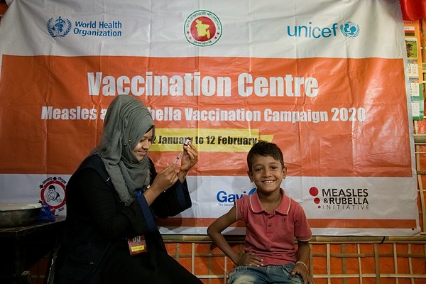 UNICEF-RR-MRVC-0954-0956  Vaccinator Razia Akter providing Measles-Rubella Vaccine to Zubair 8 years old boy inside the Rohingya Refugyee camp. Government of Bangladesh, UNICEF, WHO, Gavi and health partners are launching a massive vaccination camping to keep 300,000 Rohingya children safe. Rohingya Refugee camp-11, Balukhali, Ukhia. Cox's Bazar. Bangladesh. Photo: b.a. sujaN / UNICEF / Map
