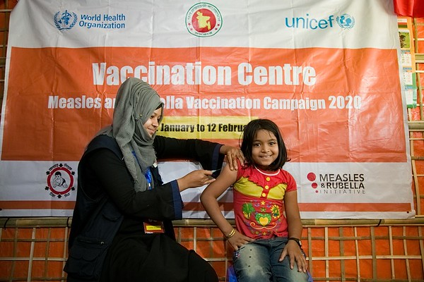 UNICEF-RR-MRVC-0948-0953  Vaccinator Razia Akter providing Measles-Rubella Vaccine to Rehana 8 years old girl inside the Rohingya Refugyee camp. Government of Bangladesh, UNICEF, WHO, Gavi and health partners are launching a massive vaccination camping to keep 300,000 Rohingya children safe. Rohingya Refugee camp-11, Balukhali, Ukhia. Cox's Bazar. Bangladesh. Photo: b.a. sujaN / UNICEF / Map