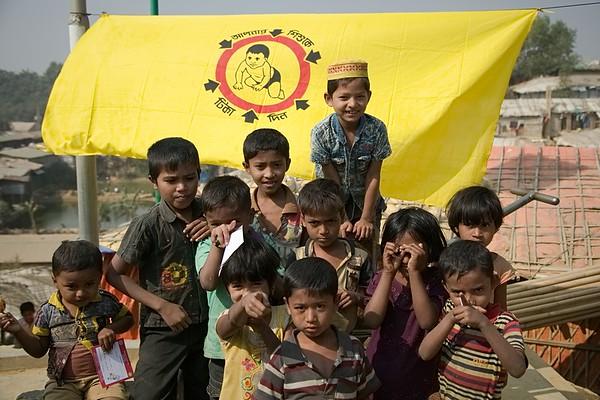 28-01-2020 Measles- Rubella Vaccination Campaign, Camp-11, Ukhia, Cox's Bazar  UNICEF-RR-MRVC-0944-0946  Group of Rohingya Children smiling in front of Vaccination campaign banner inside Rohingya Refugee camp-11, Balukhali, Ukhia. Cox's Bazar. Bangladesh. Photo: b.a. sujaN / UNICEF / Map