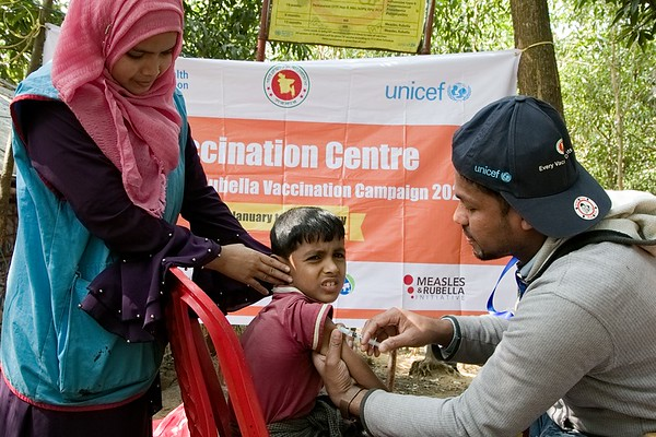 UNICEF-RR-MRVC-0165-0171 Vaccinator providing Measles- Rubella Vaccine to Rohingya Children with team Volunteer during the Campaign inside the Rohingya refugee camp.  Government of Bangladesh, UNICEF, WHO, Gavi and health partners are launching a massive vaccination camping to keep 300,000 Roningya children safe.  Camp 2, Ukhia, Cox's Bazar, Ukhia, Cox's Bazar, Bangladesh. Photo: b.a. sujaN / UNICEF / Map