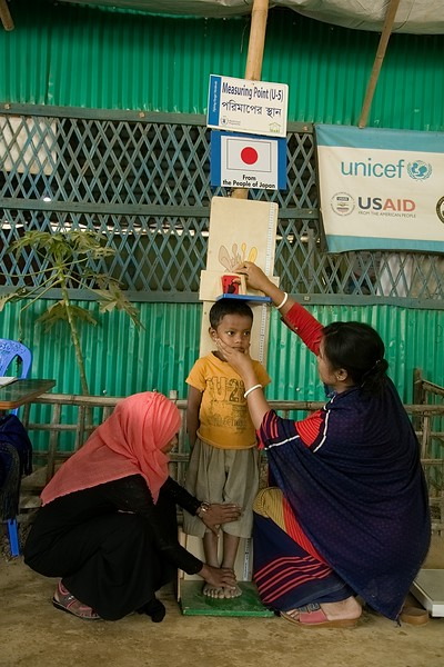 UNICEF-RR-OTP-CMAM -0673-0675  A Female Measurer taking Height Measurement of Rokibul (4) who came to visit with her mother in OTP center on Nutrition day. Funded by Japan, supported by UNICEF and Implemented by SHED. Camp-7, Balukhali, Ukhia, Cox's Bazar. Photo: b.a. sujaN / UNICEF / Map