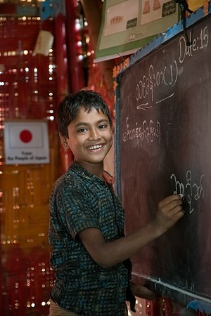 UNICEF-RR- PCLC -0317-0319  Ayasuddin is an eleven years old Rohingya child learning to write Rohingya alphabets on black board and also smiling for Photos. Pahartali Child Learning Center-2. Supported by UNICEF Funded by the people of JAPAN from Reaching out of School Children (ROSC) and (MoPME) Phase II Project. Implemented by Mukti Cox's Bazar. Camp 04, Block A-7, Ukhia, Cox's Bazar, Bangladesh. Photo: b.a. sujaN / UNICEF / Map