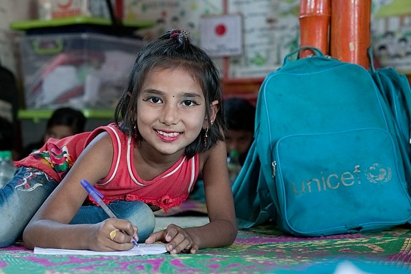 UNICEF-RR- PCLC -0322-323  Jonifa is eight years old Rohingya child writing Rohingya alphabets on copy book and also smiling for Photos. Pahartali Child Learning Center-2. Supported by UNICEF Funded by the people of JAPAN from Reaching out of School Children (ROSC) and (MoPME) Phase II Project. Implemented by Mukti Cox's Bazar. Camp 04, Block A-7, Ukhia, Cox's Bazar, Bangladesh. Photo: b.a. sujaN / UNICEF / Map