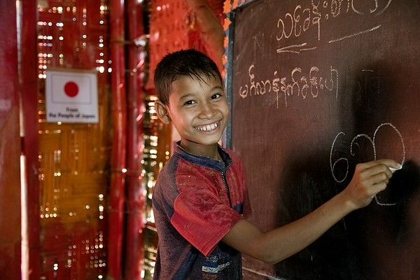 UNICEF-RR- PCLC -0315-0316  Saiful Islam is a nine-year old Rohingya child learning to write Rohingya alphabets on black board, and is also smiling for Photos. Pahartali Child Learning Center-2. Supported by UNICEF Funded by the people of JAPAN from Reaching out of School Children (ROSC) and (MoPME) Phase II Project. Implemented by Mukti Cox's Bazar. Camp 04, Block A-7, Ukhia, Cox's Bazar, Bangladesh. Photo: b.a. sujaN / UNICEF / Map