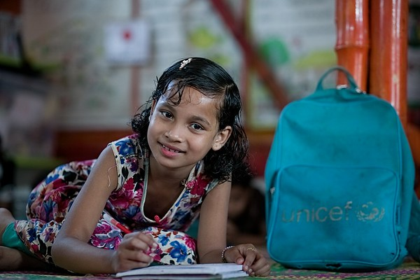 UNICEF-RR- PCLC -0320  Tohura is nine years old Rohingya child writing Rohingya alphabets on copy book and also smiling for Photos. Pahartali Child Learning Center-2. Supported by UNICEF Funded by the people of JAPAN from Reaching out of School Children (ROSC) and (MoPME) Phase II Project. Implemented by Mukti Cox's Bazar. Camp 04, Block A-7, Ukhia, Cox's Bazar, Bangladesh. Photo: b.a. sujaN / UNICEF / Map