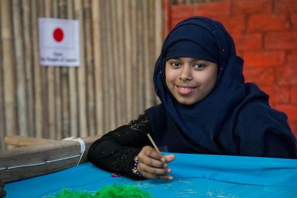 UNICEF-RR-MPC-0120-0121  Rokia, posing for photo while she is Learning Karchupi inside Multi-Purpose Child and Adolescent Center. Funded by the people of JAPAN; Supported by UNICEF; Implemented by CODEC Camp 1E, Block D, Lambashia Road, Rajapalong, Ukhia, Cox's Bazar, Bangladesh. Photo: b.a. sujaN / UNICEF / Map