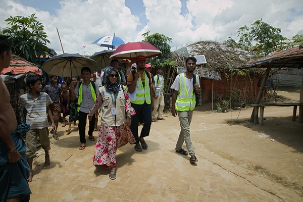 """UNICEF-0424-0429  Sharif Akhtar, 22, works for the NGO Forum based in in Camp Two. Visiting Aysha Begum (23) house with field workers during her visit inside the Rohingya Refugee Camp. She is a Hygiene Promotion outreach worker in charge of 17 volunteers.   Outreach workers supported by UNICEF play a critical role in the Rohingya refugee camps of south-eastern Bangladesh. Hundreds of such workers - many of them volunteers - venture into the camps to deliver key health messages and identify refugees who need medical attention.  UNICEF-supported NGO Forum sends numerous volunteers into the camps to provide refugees with advice on better hygiene in general and better menstrual hygiene in particular. NGO Forum also employs about 10 Rohingya teenagers to make biodegradable sanitary towels in Camp Two, a project that is now being replicated by other aid agencies elsewhere in the camps.   Sharif Akhtar, 22, works for the NGO Forum based in in Camp Two, Kutupalong camp. She is a Hygiene Promotion outreach worker in charge of 17 volunteers.   What is your job in the camps? """"I and the volunteers I lead go (all aged between 16-19) go out into the camps daily to promote our hygiene message. Every day each of us visit two households.  """"We check whether the refugees are following the sanitary advice we have given them.  If we think that that families are not being sufficiently hygienic, we will spend time giving advice to them and warning them of the dangers of getting sick because of bad hygiene.   """"The hygiene promotion we provide is not gender or age-specific. It is given to men, women and children alike. We are especially concerned about maintaining basic sanitation and concentrate on persuading people regularly to wash their hands.   """"We tailor our messages around five themes: 1) handwashing; 2) sanitation, 3) water safety; 4) MHM awareness and 5) Acute Watery Diahorrea (AWD) awareness. """"When I go to the households, I see the problems and I enjoy finding solutions. I feel pr"""