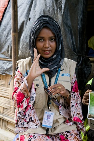 """UNICEF-0415-0417  Sharif Akhtar, 22, works for the NGO Forum based in in Camp Two. Discussing with field worker during her visit inside the Rohingya Refugee Camp. She is a Hygiene Promotion outreach worker in charge of 17 volunteers.   Outreach workers supported by UNICEF play a critical role in the Rohingya refugee camps of south-eastern Bangladesh. Hundreds of such workers - many of them volunteers - venture into the camps to deliver key health messages and identify refugees who need medical attention.  UNICEF-supported NGO Forum sends numerous volunteers into the camps to provide refugees with advice on better hygiene in general and better menstrual hygiene in particular. NGO Forum also employs about 10 Rohingya teenagers to make biodegradable sanitary towels in Camp Two, a project that is now being replicated by other aid agencies elsewhere in the camps.   Sharif Akhtar, 22, works for the NGO Forum based in in Camp Two, Kutupalong camp. She is a Hygiene Promotion outreach worker in charge of 17 volunteers.   What is your job in the camps? """"I and the volunteers I lead go (all aged between 16-19) go out into the camps daily to promote our hygiene message. Every day each of us visit two households.  """"We check whether the refugees are following the sanitary advice we have given them.  If we think that that families are not being sufficiently hygienic, we will spend time giving advice to them and warning them of the dangers of getting sick because of bad hygiene.   """"The hygiene promotion we provide is not gender or age-specific. It is given to men, women and children alike. We are especially concerned about maintaining basic sanitation and concentrate on persuading people regularly to wash their hands.   """"We tailor our messages around five themes: 1) handwashing; 2) sanitation, 3) water safety; 4) MHM awareness and 5) Acute Watery Diahorrea (AWD) awareness. """"When I go to the households, I see the problems and I enjoy finding solutions. I feel proud because when I sta"""