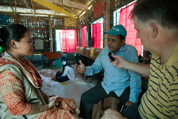"""UNICEF-0430-0431  Magdalene Tripura, 33, NGO Forum Menstrual Hygiene Manger (MHM). Alastair Lawson Tancred and Mr. Mostofa from UNICEF Bangladesh Taking Interview,  Magdalene Tripura, 33, NGO Forum Menstrual Hygiene Manger (MHM) """"My job is to run the MHM programme. I have 11 volunteers under me - I send them to camp households as well as visit myself. How receptive is the refugee community to your MHM message? """"The day before we visit, we notify the refugees that we are coming and get their permission to do so. The next day we go to the shelters and try to gather 12 to 15 women and young females aged between 18-45. We also look after younger adolescent girls. When we sit with them, a whole array of problems come out. Typically it may be water shortage problems which we try and help them sort out, before moving on to more sensitive subjects such as MHM. You deliver your MHM message to separated age groups?  """"We have to address everyone who is of menstruating age. But it's much better to do this in separate sessions, because a daughter-in-law maybe embarrassed to discuss such matters in front of her mother-in-law and vice versa. Do you have to battle against rumour and myth in relation to the delivery of you MHM message?  """"At the beginning we do not go to the MHM issue because it's so taboo. We have to approach the subject gradually, usually by discussing general hygiene issues at first. Only after we have won the confidence of the refugees do we move on to the more sensitive issues.  It must be very difficult for a young girl who is experiencing her first menstrual cycle in the camps? """"That is why we try to involve a girl's mother, so that she can prepare her daughter for what lies ahead. We have 11 volunteers in Camp Two, daily distributing about 70 sanitary napkin packs (10 in each pack) that we have made at our centre. It much less embarrassing for young girls to be given sanitary towels in the safety of their homes than it is for them to venture outside to get th"""