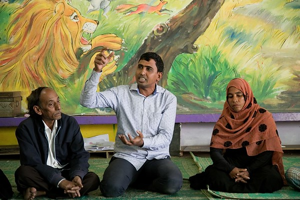 UNICEF- CBCPC 0121-0122  Iqbal Hossain, NGO worker and member of Community-Based Child Protection Committees (CBCPCs), discusses the impact of deforestation on the host community as a result of the Rohingya humanitarian crisis during a monthly meeting with parents and host community members at a Child Friendly Space in Balukhali.  UNICEF provides support to host-community children and adolescents through its 10 Child-Friendly Spaces (CFS) and 90 Adolescent Clubs (AC) in the host community. UNICEF reaches 9,000 children and 4,000 adolescents at these facilities. Parents and care givers of the children and adolescents take part in Community-Based Child Protection Committees (CBCPCs). The CBCPCs serve as platforms to improve community awareness on child protection to prevent violence, abuse, neglect and exploitation. They serve as a watchdog and first line of reporting abuse, while referring survivors for counselling and services. In total, 83 members from CBCPCs are working to improve the protective environment for children and adolescents.   Balukhali, Teknaf, Cox's Bazar. Photo: b.a.sujaN / UNICEF / Map