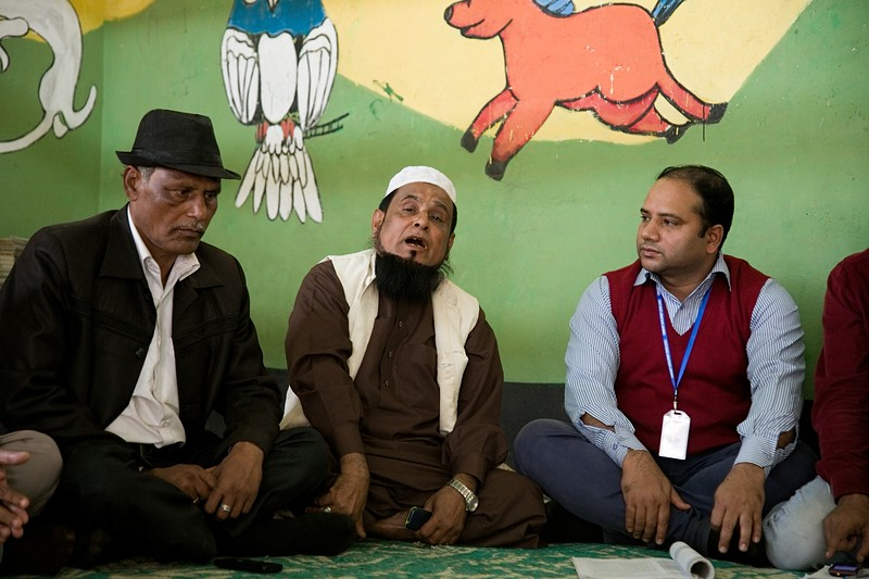 UNICEF- CBCPC -0117-0118  Moulana Abdul Kader, a religious leader from the host community and respected member of the Community-Based Child Protection Committee (CBCPC), discusses with fellow committee members about child marriage and impact of drug use and drug trafficking in the host community.  UNICEF provides support to host-community children and adolescents through its 10 Child-Friendly Spaces (CFS) and 90 Adolescent Clubs (AC) in the host community. UNICEF reaches 9,000 children and 4,000 adolescents at these facilities. Parents and care givers of the children and adolescents take part in Community-Based Child Protection Committees (CBCPCs). The CBCPCs serve as platforms to improve community awareness on child protection to prevent violence, abuse, neglect and exploitation. They serve as a watchdog and first line of reporting abuse, while referring survivors for counselling and services. In total, 83 members from CBCPCs are working to improve the protective environment for children and adolescents.   Balukhali, Teknaf, Cox's Bazar. Photo: b.a.sujaN / UNICEF / Map
