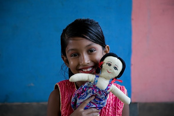 UNICEF- CFS 0153-0155  Mukta Tahere (8), with her doll Sumaya.  Mukta attends a UNICEF Child Friendly Space each day in Balukhali. UNICEF supports 9,000 host-community children through 10 Child-Friendly Spaces (CFS). These spaces provide safe, enabling environments for children to learn, grow and play. Psychosocial support and case management services are also provided at the CFS if required. Children receive life-skills education at the CFS to help them learn about child rights and child protection. They enjoy recreational games, drama, cultural activities such as drama, singing and dancing.  Balukhali, Teknaf, Cox's Bazar. Photo: b.a.sujaN / UNICEF / Map