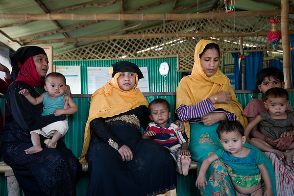 UNICEF-OTP-0282-0289  Mothers and children waiting inside a UNICEF supported Outpatient Therapeutic Programmes (OTP) in the Rohingya refugee camps.   UNICEF and partners operate 33 outpatient therapeutic programmes (OTPs) to treat malnutrition in children under 5 in the Rohingya refugee camps. In 2018, 21,000 children were admitted to UNICEF supported OTPs and treated for severe acute malnutrition. The OTP cure rate was over 96 per cent. Overall, the malnutrition rate has reduced. However, contributing factors such as poverty, lack of dietary diversity, nutrient deficiency and access to safe water and sanitation remain a challenge to reduce malnutrition rates further.   Teknaf, Cox's Bazar. Photo: b.a.sujaN / UNICEF / Map