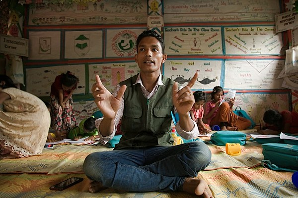 UNICEF-RR-0318 – 0321      MD Sadek (20) is sharing his experience How he flew to Bangladesh from Myanmar. DAM Learning Centre, Block-C, Camp-7.  Photo: b.a.sujaN / UNICEF / Map