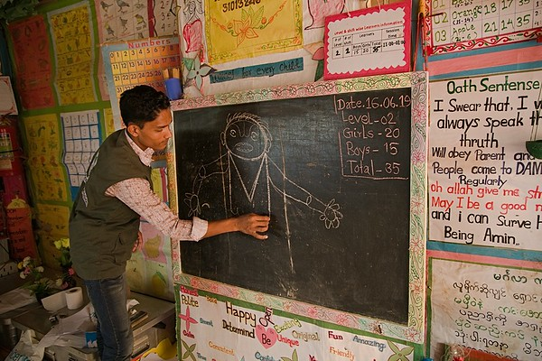 UNICEF-RR-0326 – 0329 MD Sadek (20) is demonstrating students how they can draw picture with words. DAM Learning Centre, Block-C, Camp-7.  Photo: b.a.sujaN / UNICEF / Map