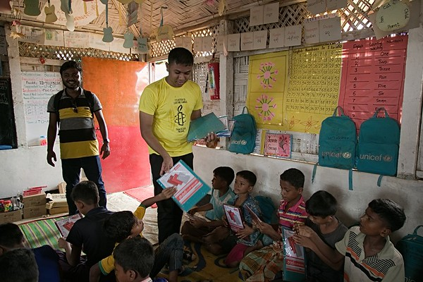UNICEF-RR-0058-0061  Representative from Amnesty International is distributing art materials to Rohingya children to draw their dreams.   Kutupalang Registered Camp-2W, block D-3W, Ukhiya, Cox's Bazar Photo: b.a.sujaN / UNICEF / Map
