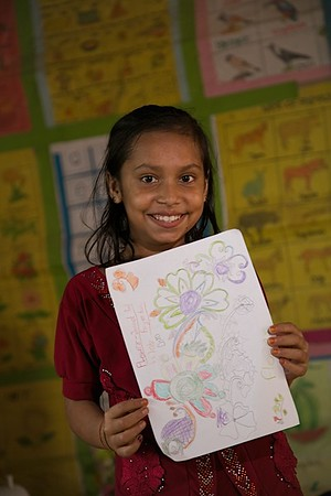 UNICEF-RR-0305 – 0306  Jannatul Ferdous (10) showing her colorful flower drawing. DAM Learning Centre, Block-C, Camp-7.  Photo: b.a.sujaN / UNICEF / Map