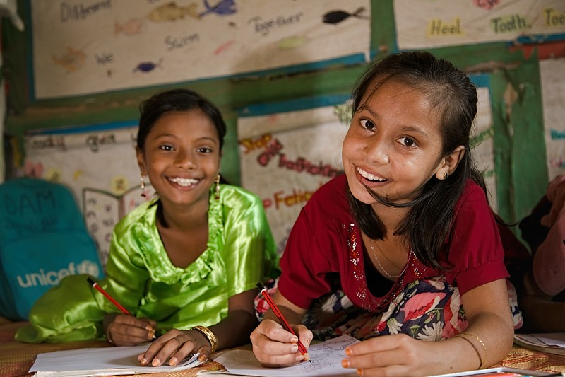 UNICEF-RR-0304  Jannatul Ferdous (10) and Jainob Bibi (8) delivers their happy smile while drawing at LC. DAM Learning Centre, Block-C, Camp-7.  Photo: b.a.sujaN / UNICEF / Map