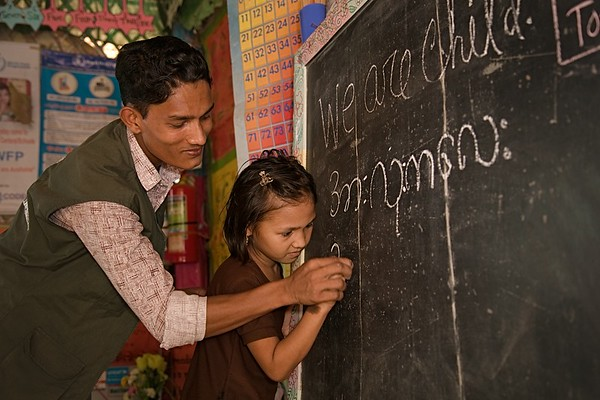 UNICEF-RR-0291 - 0293 Teacher MD Sadek (20) helps to write translate English words to Burmese language to Umaema (8) in blackboard at the LC. DAM Learning Centre, Block-C, Camp-7.  Photo: b.a.sujaN / UNICEF / Map