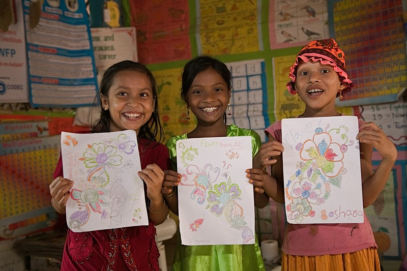 UNICEF-RR-0307 - 0308 Boshara (8) with her best friends Jannatul Ferdous (10) and Jainob Bibi (8) showing drawing with a smiling face. DAM Learning Centre, Block-C, Camp-7.  Photo: b.a.sujaN / UNICEF / Map